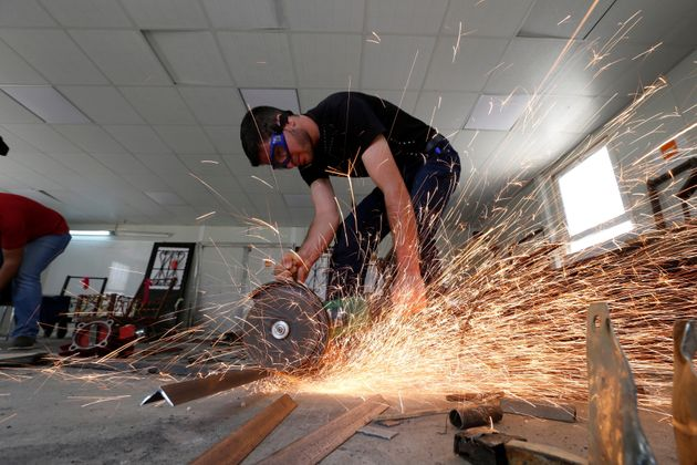 Syrian refugee metal shop trainees work at one of the vocational training centers in the Azraq camp, June...