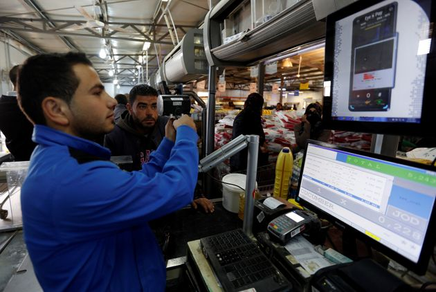 A Syrian refugee uses an IrisGuard machine to verify his identity and receive food aidat the Tazweed...