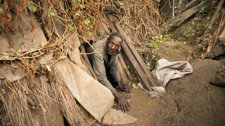 A man crawls out of the cave he has inhabited for decades in Kenya's Great Rift Valley. Several hundred people live in caves