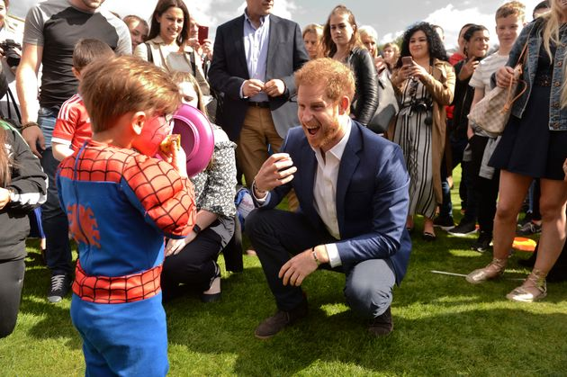 Prince Harry speaking to a young