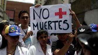"""Demonstrators hold a banner that reads """"No more deaths"""" as they take part in a rally of workers of the health sector against President Nicolas Maduro's government in Caracas, Venezuela May 17, 2017. REUTERS/Marco Bello"""