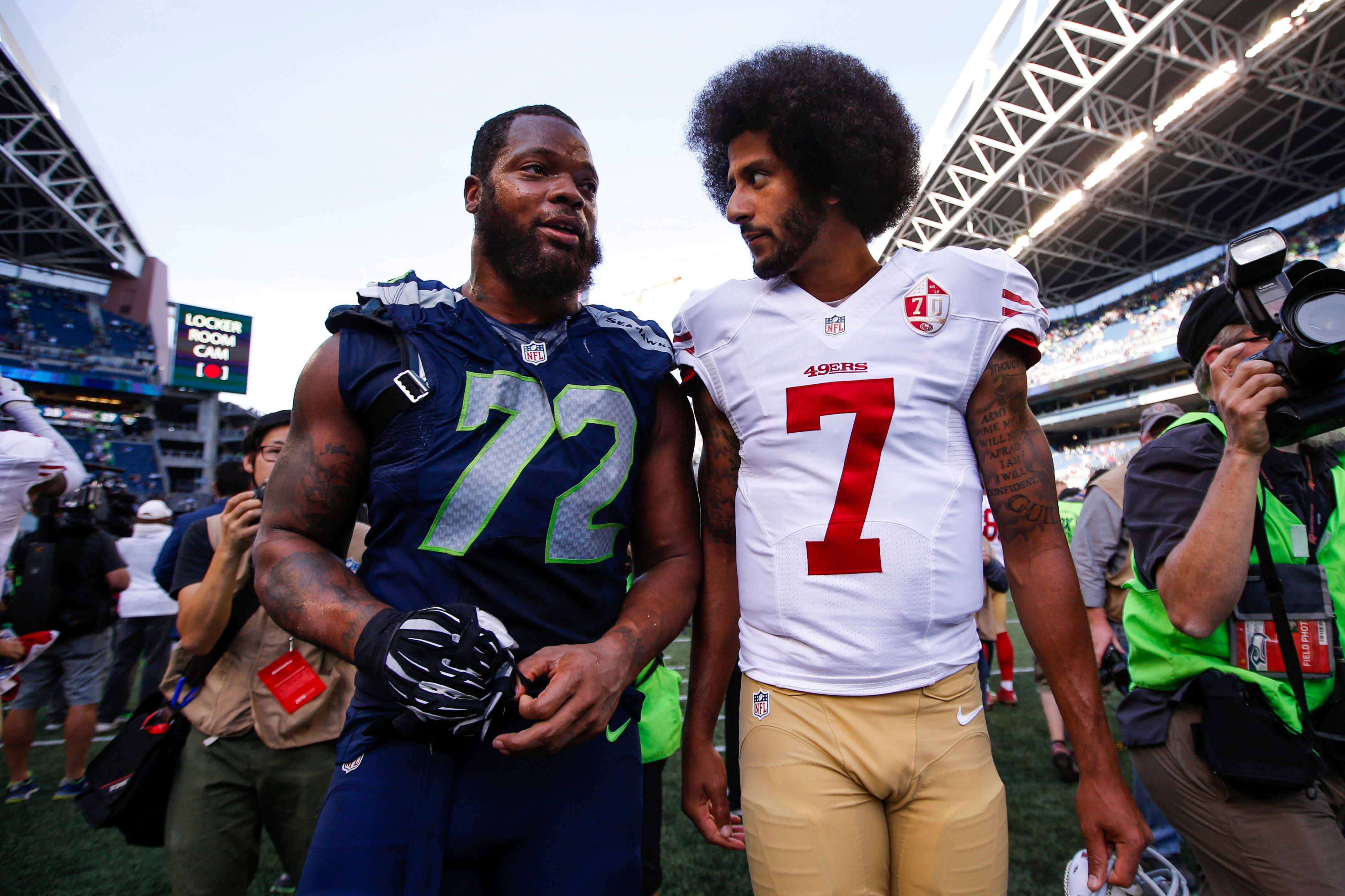 Sep 25, 2016; Seattle, WA, USA; San Francisco 49ers quarterback Colin Kaepernick (7) and Seattle Seahawks defensive end Michael Bennett (72) talk following a 37-18 Seattle victory at CenturyLink Field. Mandatory Credit: Joe Nicholson-USA TODAY Sports