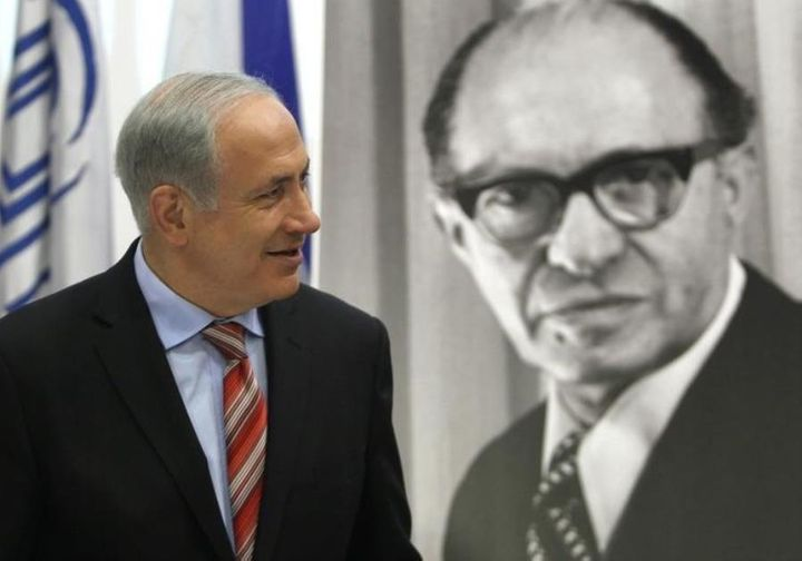 <em>Prime Minister Benjamin Netanyahu walks in front of a poster of the late Prime Minister Menachem Begin upon his arrival a