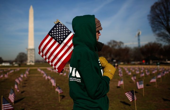 Iraq war veteran Sara Poquette helps set up 1,892 American flags on the National Mall March 27, 2014 in Washington, DC. The I