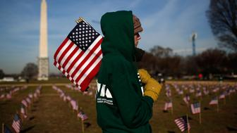 WASHINGTON, DC - MARCH 27:  Iraq war veteran Sara Poquette helps set up 1,892 American flags on the National Mall March 27, 2014 in Washington, DC. The Iraq and Afghanistan Veterans of America installed the flags to represent the 1,892 veterans and service members who committed suicide this year as part of the 'We've Got Your Back: IAVA's Campaign to Combat Suicide.'  (Photo by Win McNamee/Getty Images)