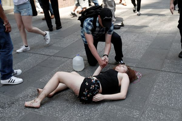 An injured woman lies on the sidewalk in Times Square after a speeding vehicle struck pedestrians on the sidewalk.