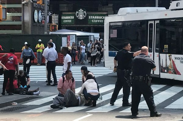 First responders at the scene as people help injured pedestrians.
