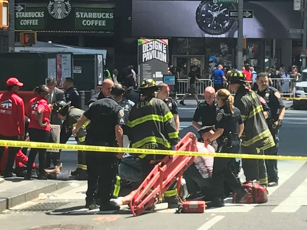 First responders assist injured pedestrians after a vehicle struck pedestrians on a sidewalk in Times Square.