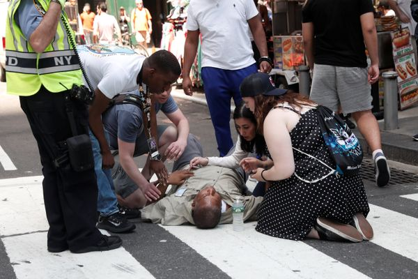 An injured man is seen on the sidewalk in Times Square.
