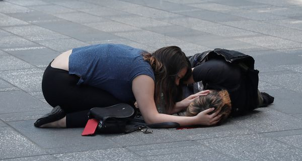 A woman attends to an injured man on the sidewalk in Times Square.