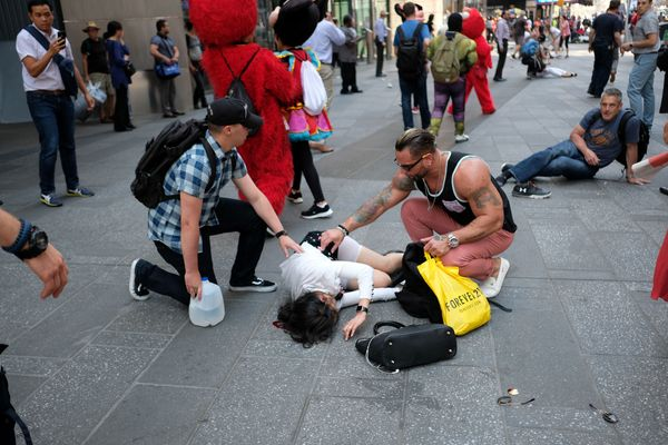 People attend to injured pedestrians after a car plunged into them in Times Square.