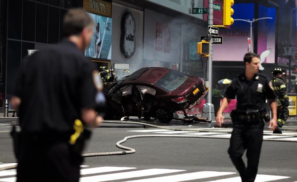 Police secure an area near a car after it plunged into pedestrians in Times Square.