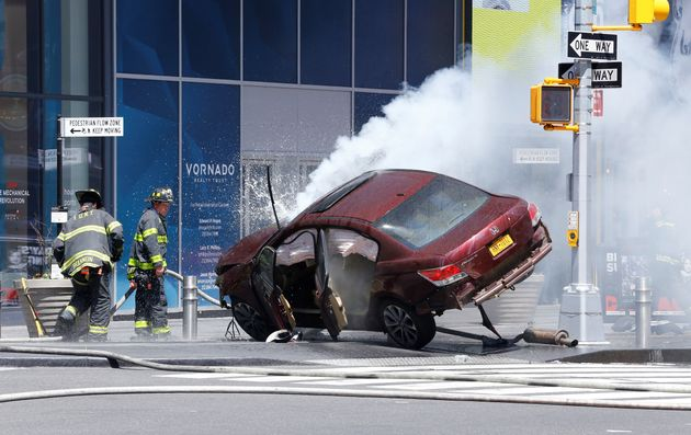 Flames and smoke rises from a wrecked vehicle after it ploughed into pedestrians on a busy sidewalk on...