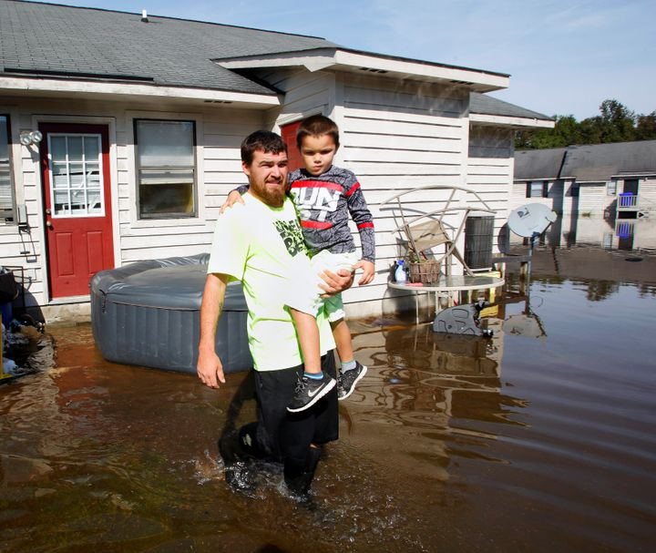 A man carries his son through flood waters surrounding their Greenville, North Carolina, home on Oct. 14, 2016, in the a