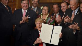 WASHINGTON, D.C. - APRIL 26: (AFP-OUT) US President Donald Trump displays the signed 'Antiquities Executive Order' as Interior Secretary Ryan Zinke (L) and Utah Sen. Orrin Hatch (R) join others at the Department of the Interior, on April 26, 2017 in Washington, DC. Interior will review prior monument designations made by former Presidents Barack Obama, George W. Bush and Bill Clinton. (Photo by Mike Theiler-Pool/Getty Images)