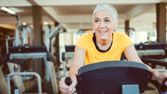 Mature woman exercising in local gym. She is using exercise bike. Listening music while exercising.