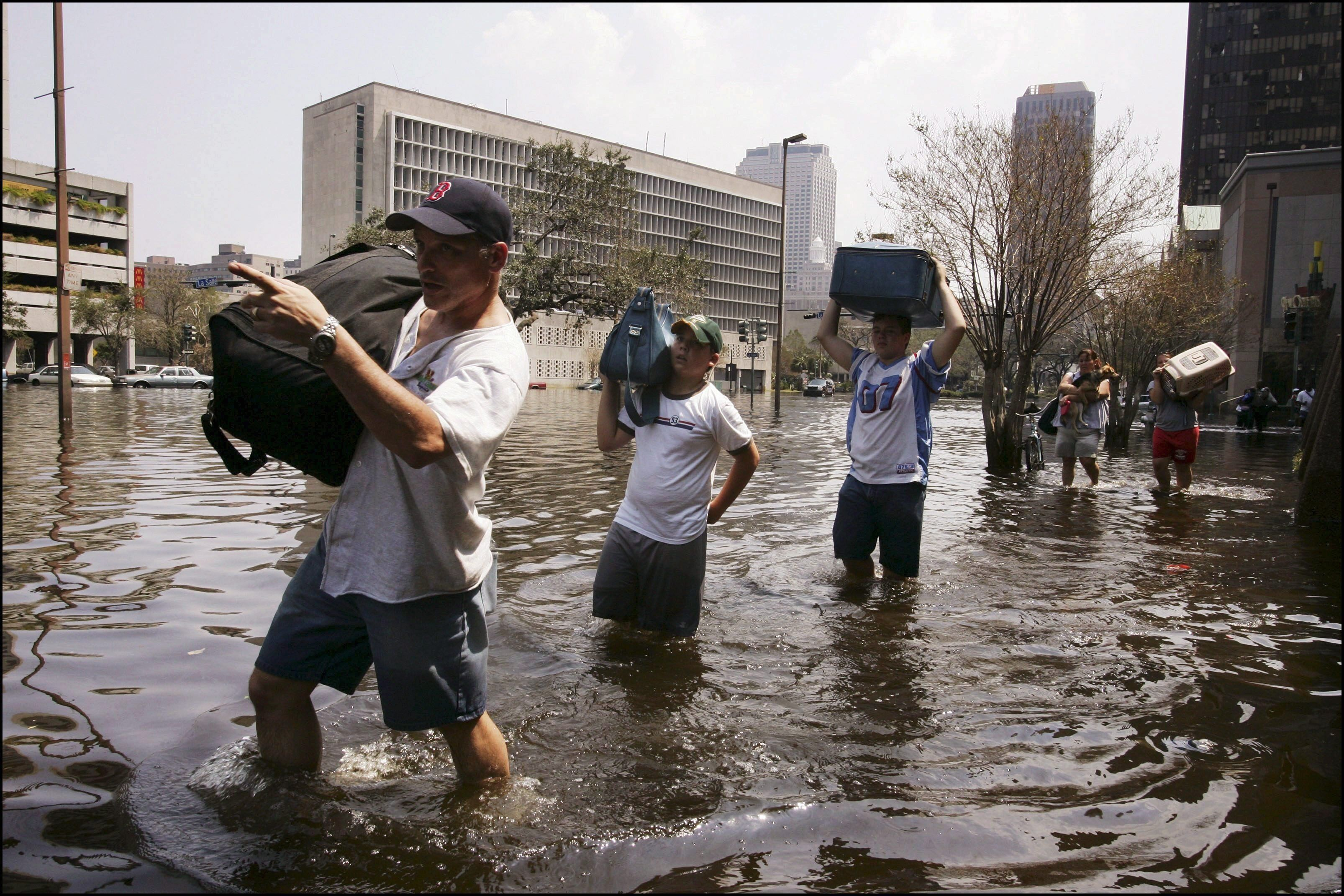 Survivors of Hurricane Katrina evacuate their homes on Sept. 3,