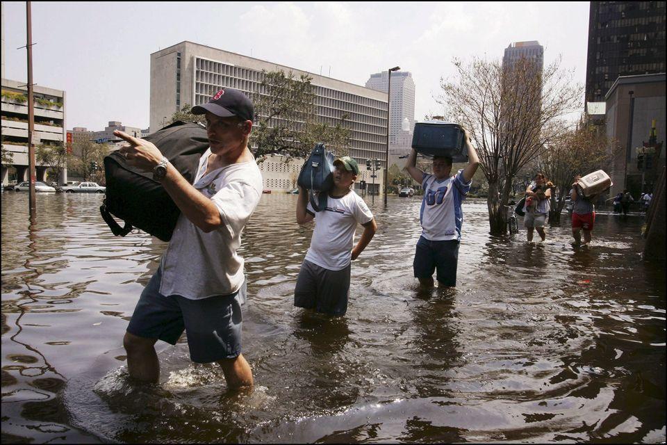 Survivors of Hurricane Katrina evacuate their homes on Sept. 3,