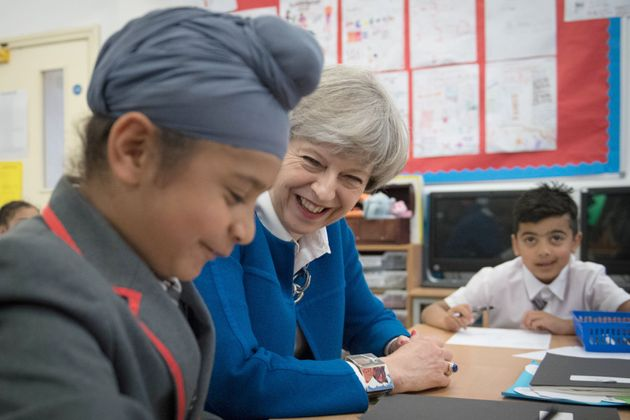 Theresa May with eight-year-old Akaal Singh at Nishkam Primary School in