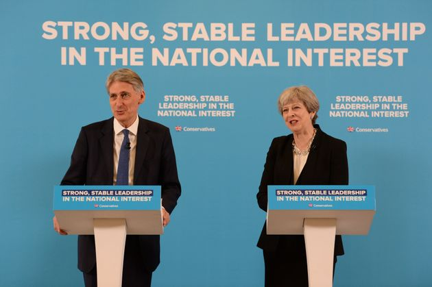 Theresa May and Philip Hammond speaking in front of a subtle campaign