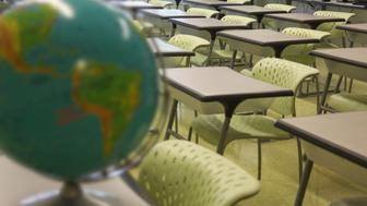 An empty classroom with rows of desks with a globe in foreground.