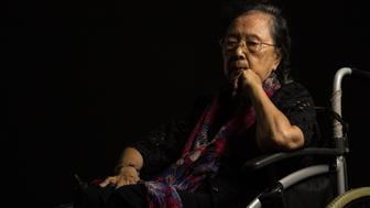 Asian elder woman in her wheelchair feeling lonely on black background
