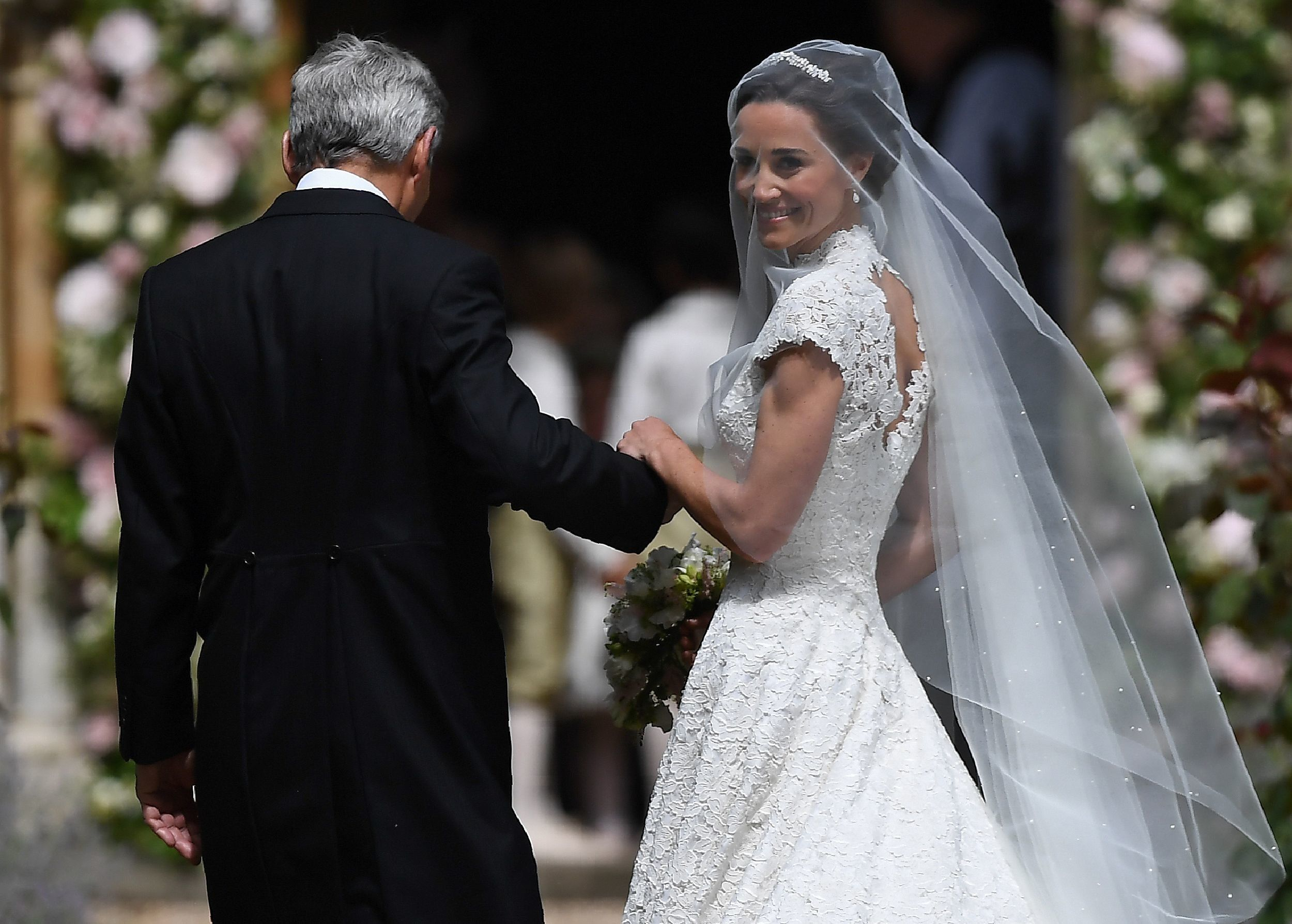 Pippa Middleton, (R) is escorted by her father Michael Middleton, as she arrives for her wedding to James Matthews at St Mark's Church in Englefield, west of London, on May 20, 2017. Pippa Middleton hit the headlines with a figure-hugging outfit at her sister Kate's wedding to Prince William but now the world-famous bridesmaid is becoming a bride herself. Once again, all eyes will be on her dress as the 33-year-old marries financier James Matthews on Saturday at a lavish society wedding where William and Kate's children will play starring roles. / AFP PHOTO / POOL / Justin TALLIS        (Photo credit should read JUSTIN TALLIS/AFP/Getty Images)
