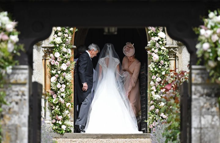 Duchess Kate, in a pale pink dress, adjusted Pippa's gown.