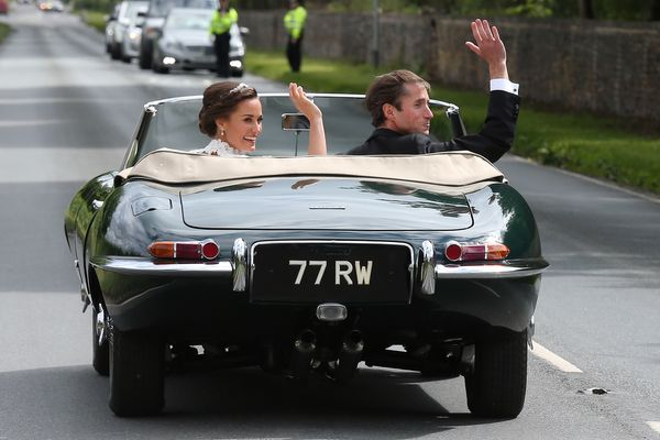 The bride and groom leave in a classic car.