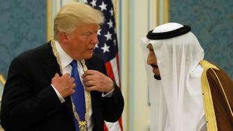 Saudi Arabia's King Salman bin Abdulaziz Al Saud (R) presents U.S. President Donald Trump with the Collar of Abdulaziz Al Saud Medal at the Royal Court in Riyadh, Saudi Arabia May 20, 2017. REUTERS/Jonathan Ernst