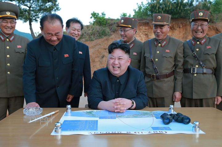 North Korean leader Kim Jong-un laughs during a test launch of a ground-to-ground medium long-range strategic ballistic rocke
