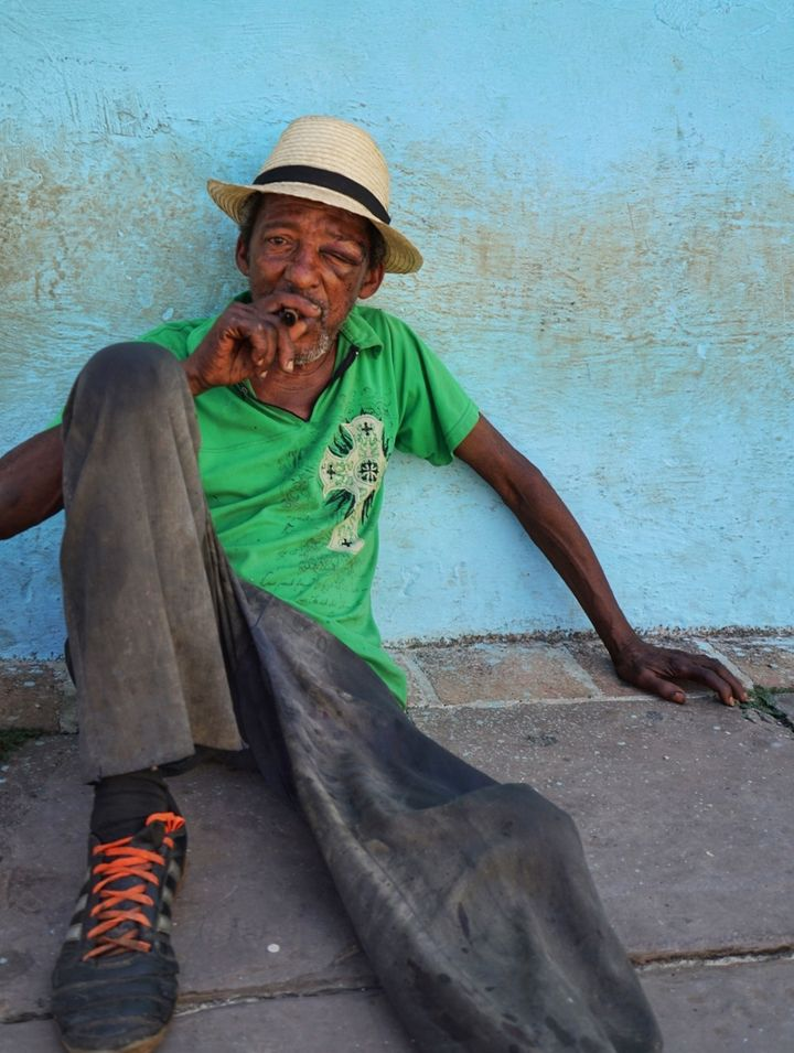 <p>A man sits outside catching a breeze and enjoying a Cuban cigar in Trinidad</p>