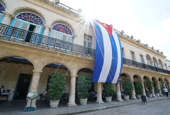 <p>The sun glows bright behind the Cuban flag in Old Havana</p>
