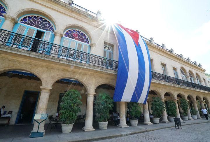 The sun glows bright behind the Cuban flag in Old Havana