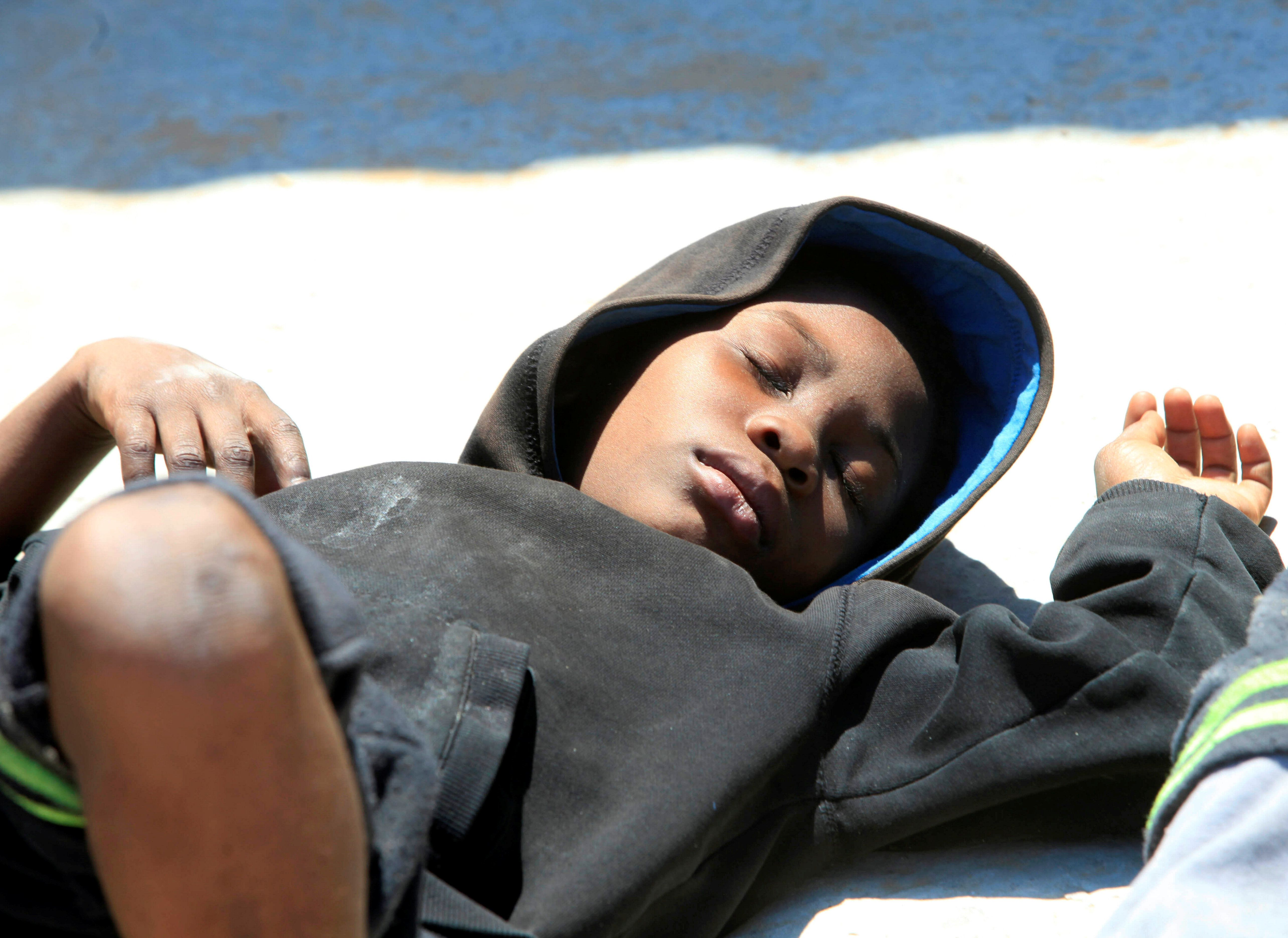 An illegal migrant sleeps at Gasr Garabulli port after he was rescued by Libyan Coast Guard, east of Tripoli, Libya, May 18, 2017. REUTERS/Ismail Zitouny