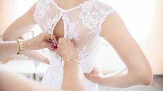 Mother helping the bride - her daughter to put her wedding dress on, close up photo