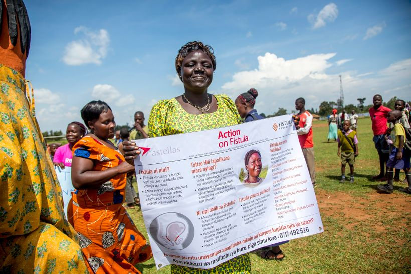 An outreach worker holds a sign about fistula at an Action on Fistula.