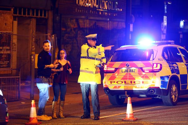 Police stand by a cordoned off street close to the Manchester Arena.