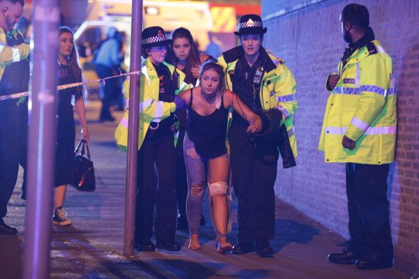 Police and other emergency services assist a victim near the Manchester arena.
