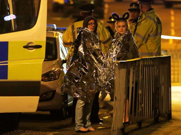 Two women wrapped in formal blankets stand near the Manchester Area where a lone male attacker detonated...