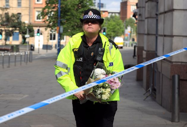 A police officer moves a floral tribute close to the Manchester