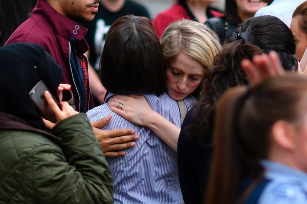Retail staff hug each other after being evacuated from the Arndale Centre shopping mall in Manchester following a security al