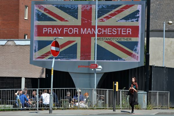 "A woman walks past an electronic advertising board displaying a Union Flag and the words ""Pray For Manchester"" near the Manch"
