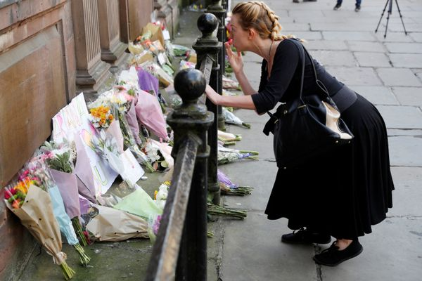 A woman blows a kiss after laying flowers for the victims of the Manchester Arena attack.
