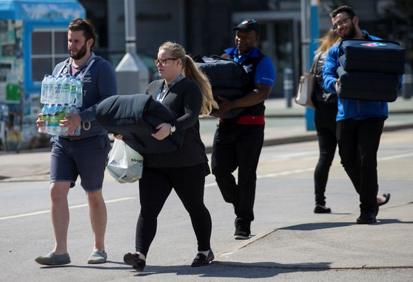 People carry food and water to a support center at Manchester City soccer team's Etihad Stadium.