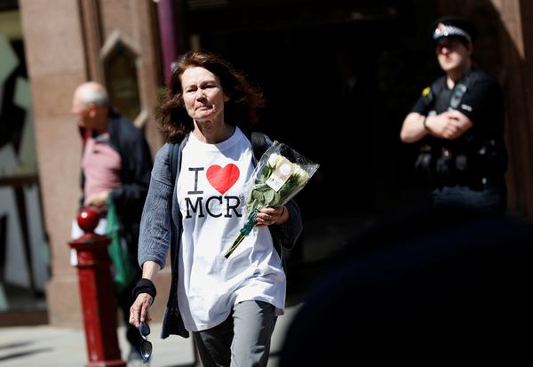 A woman lays flowers for the victims of the Manchester Arena attack, in central Manchester.