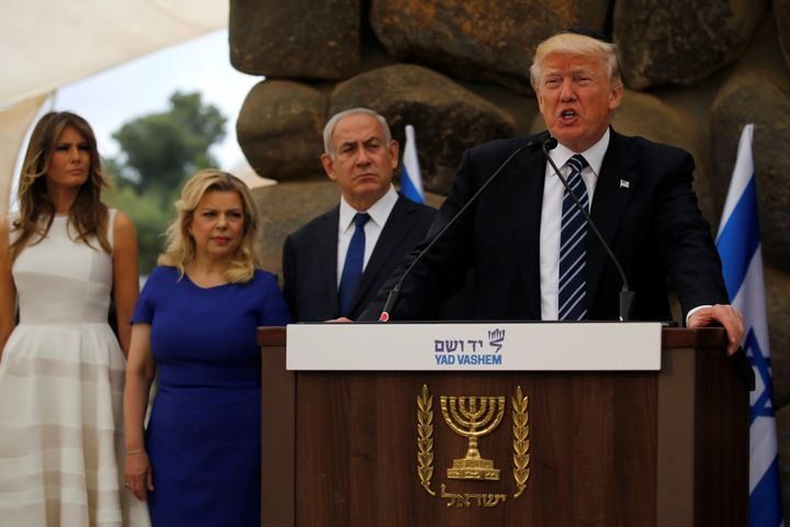 U.S. President Donald Trump, flanked by Israel's Prime Minister Benjamin Netanyahu (3rd L) and their wives Melania Trump (L) and Sara Netanyahu (2nd L), delivers remarks after a wreath-laying at the Yad Vashem holocaust memorial in Jerusalem May 23, 2017.