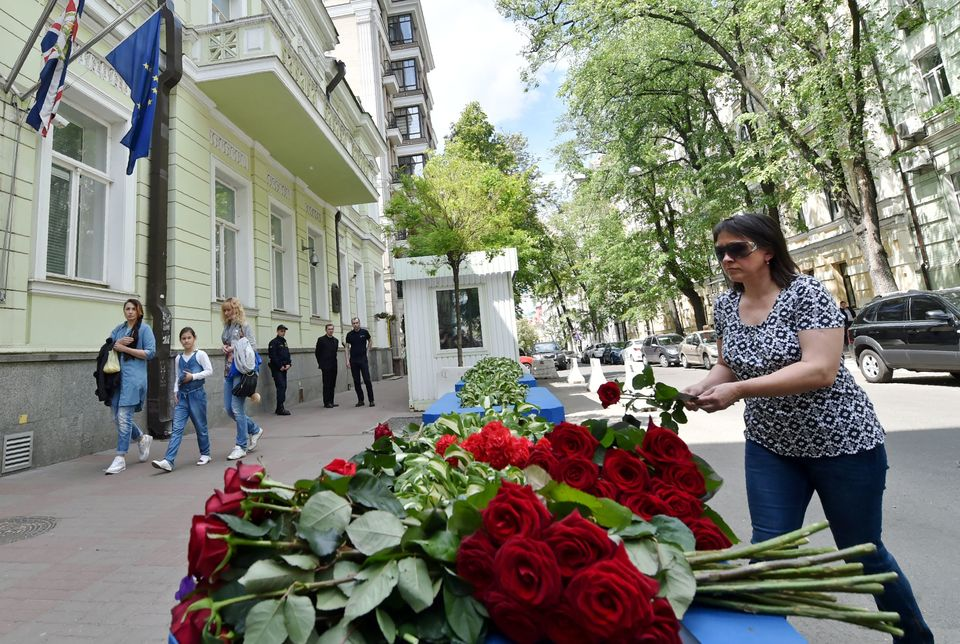 A woman lays flowers in front of the British embassy in Kiev.