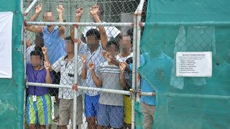 Asylum-seekers look through a fence at the Manus Island detention centre in Papua New Guinea March 21, 2014.    AAP/Eoin Blackwell/via REUTERS     ATTENTION EDITORS - THIS PICTURE WAS PROVIDED BY A THIRD PARTY. EDITORIAL USE ONLY. NO RESALES. NO ARCHIVE. AUSTRALIA OUT. NEW ZEALAND OUT.