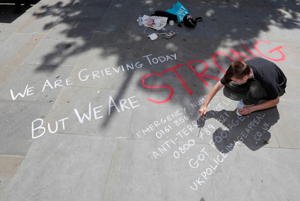 A man writes a message on the pavement in central Manchester.